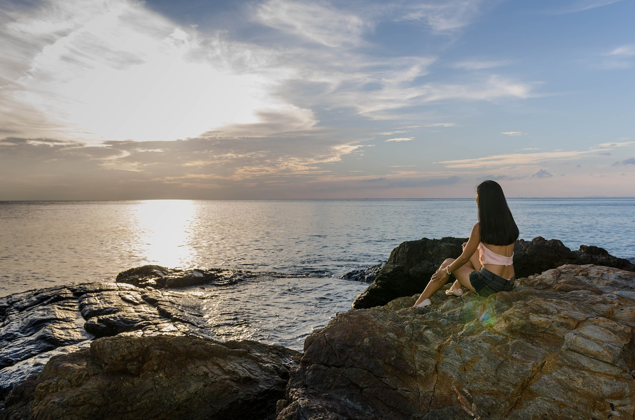 Girl sitting on rock looking at the ocean