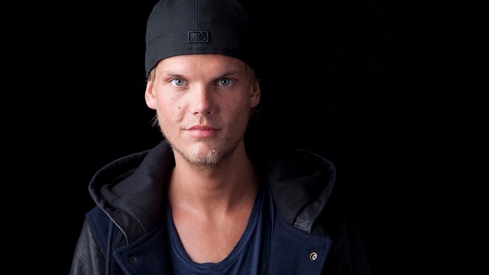 Deceased singer Avicii against a black background looking into the camera prior to mental health crisis