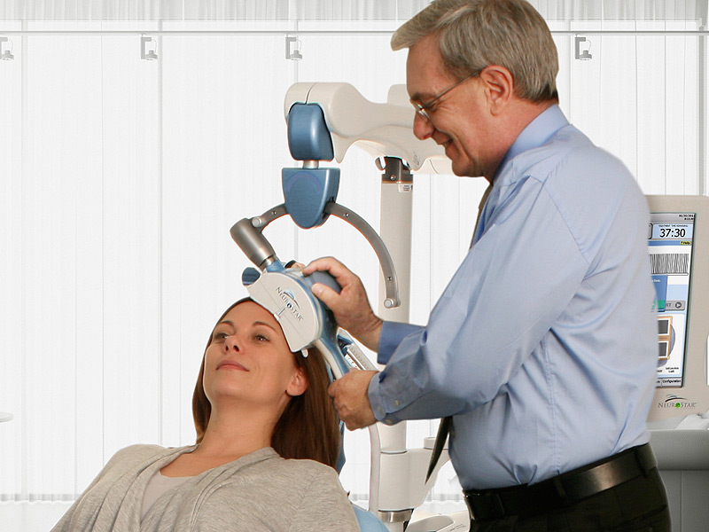 TMS technician applies TMS therapy with NeuroStar