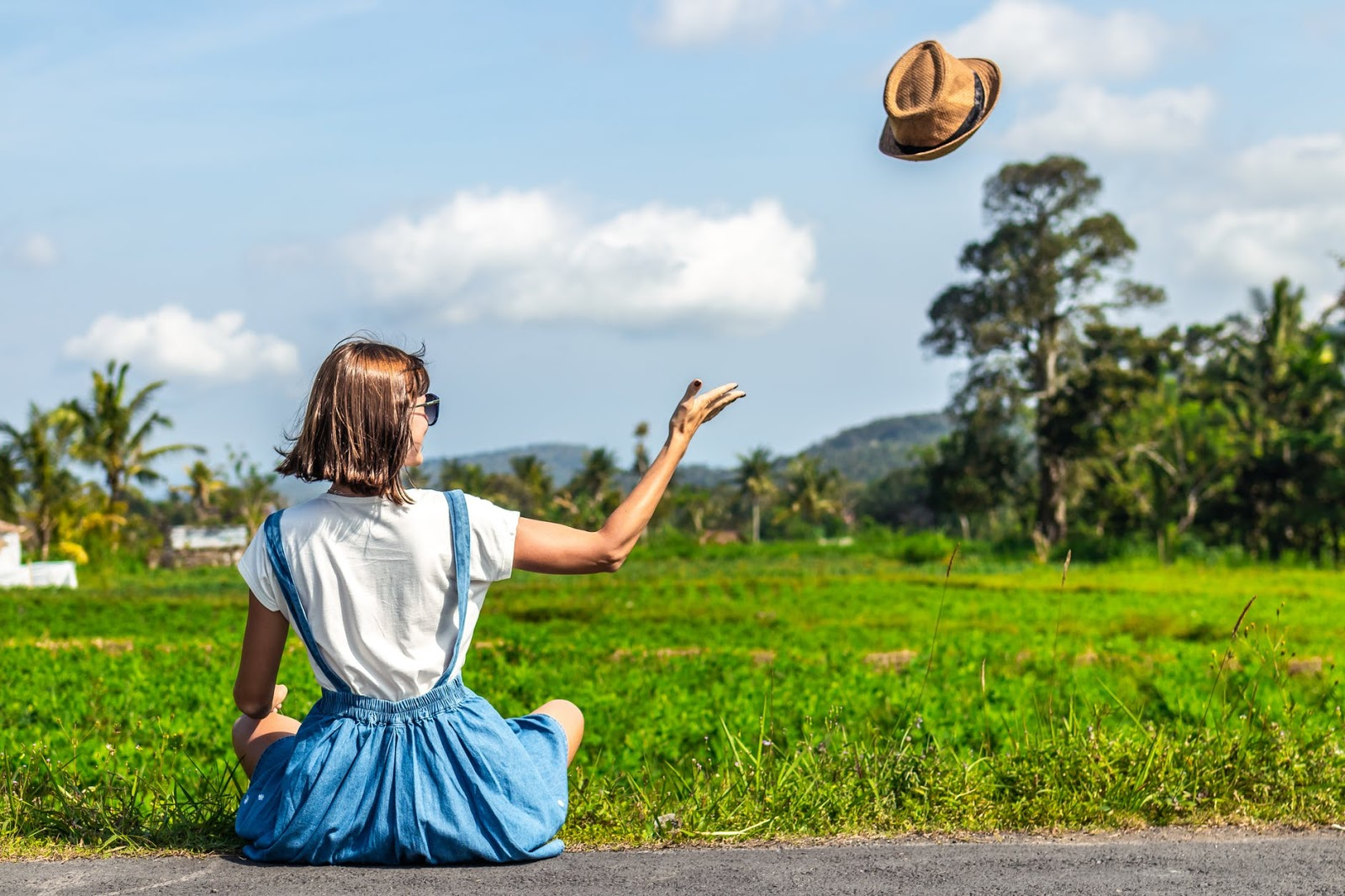 A girl in a blue skirt sits cross legged in a field and throws her hat into the air with a sense of freedom