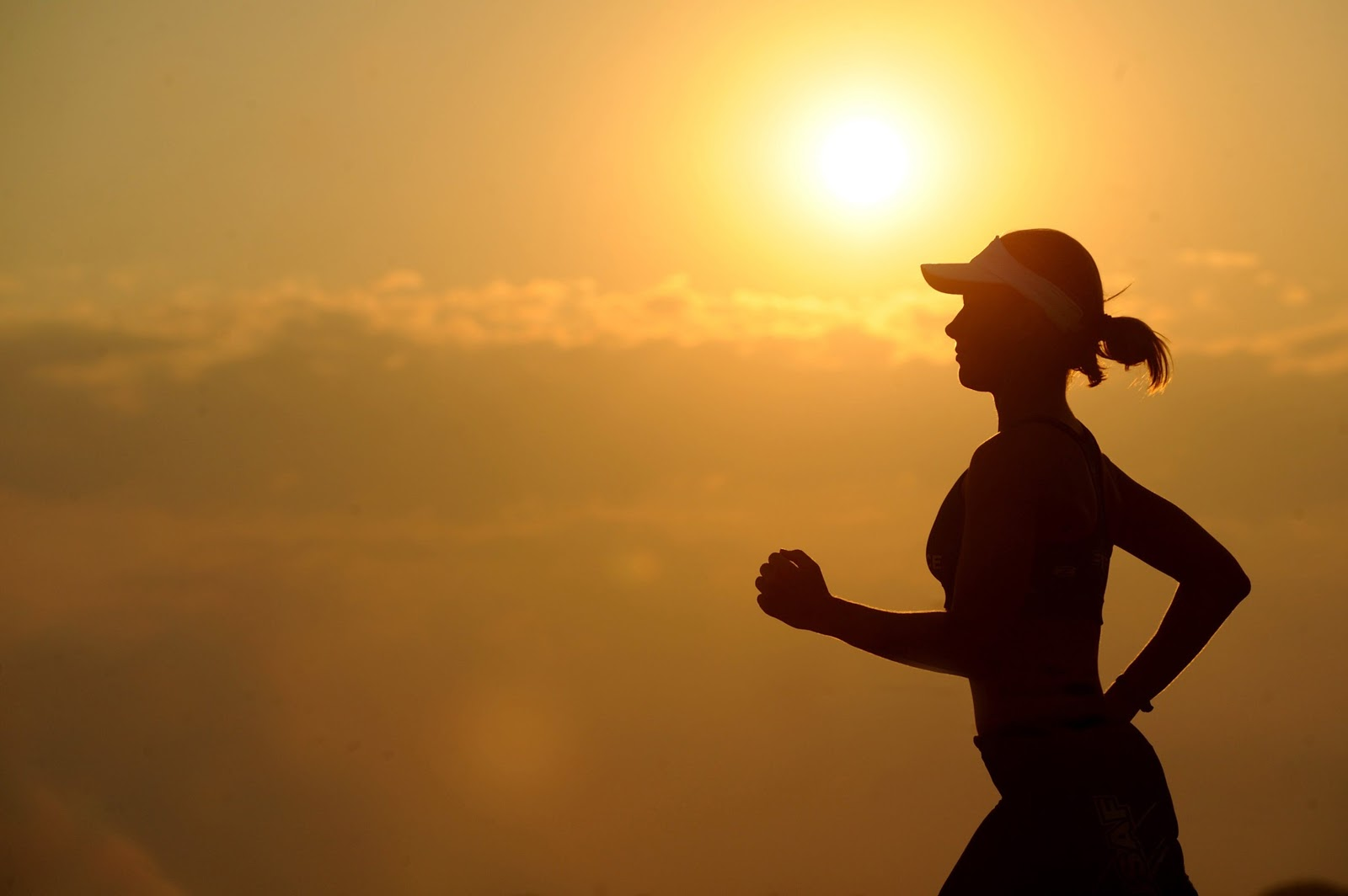 The silhouette of a woman exercising in the morning to help treat her insomnia.