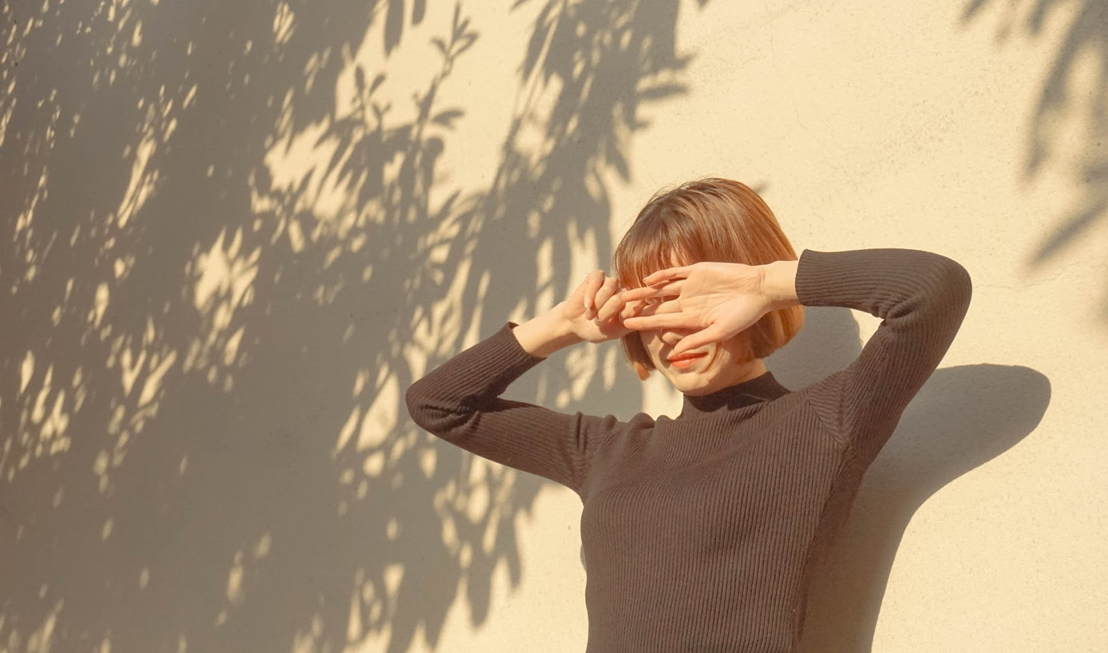 A woman stands in the sun and holds her hands over her eyes to protect her from the light.