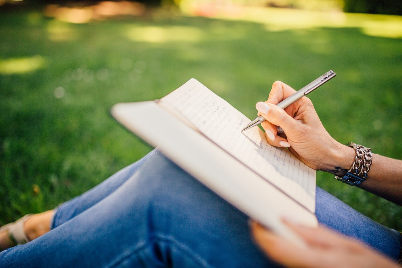 A woman is journaling, which is one strategy that can be used to cope with symptoms of existential depression.