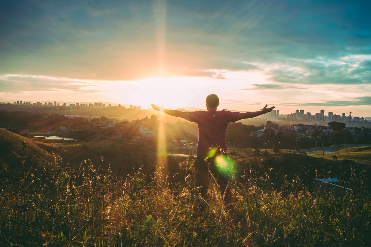 A man stands on top of a hill with his arms spread out, appearing to be feeling euphoric and in a positive mood.