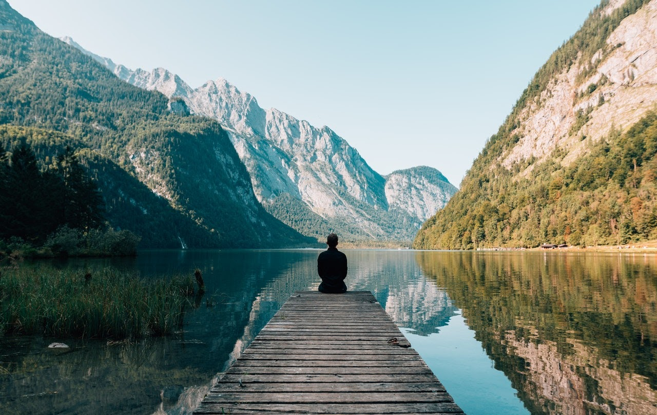 A man sits on a bridge looking out at a mountain landscape. He appears to be tranquil and in a peaceful state.