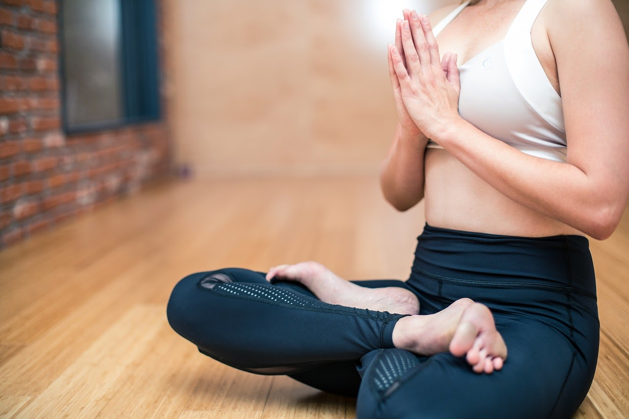 A woman is sitting and doing yoga meditation, a great strategy for coping with the physical symptoms of anxiety.
