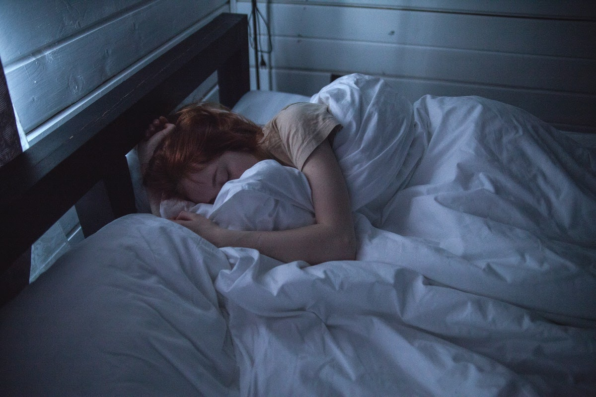 A woman is in bed appearing to be extremely fatigued, which is one of the physical symptoms that grief can cause.