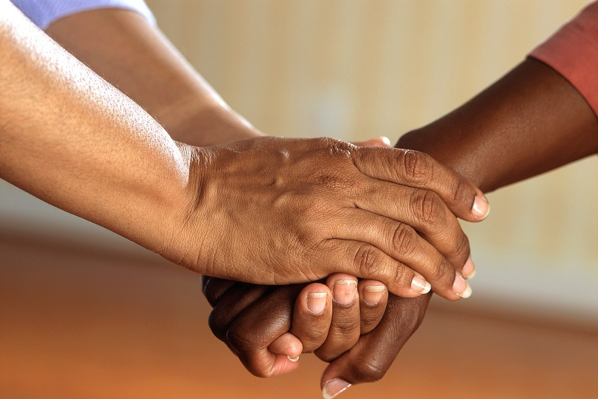 One person appears to be holding another person's hands in a supportive manner. Relying on loved ones and finding support in this way is one method for dealing  with grief.