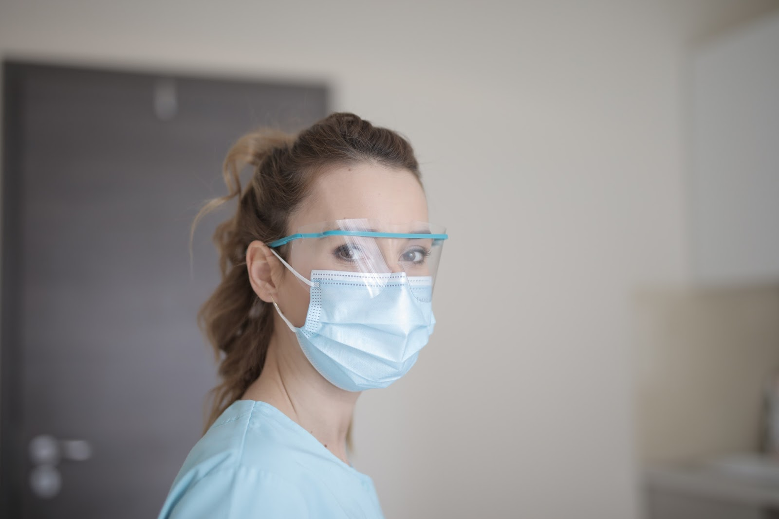A healthcare worker wears a face shield and surgical mask, which are considered to be proper PPE for protection against COVID-19.