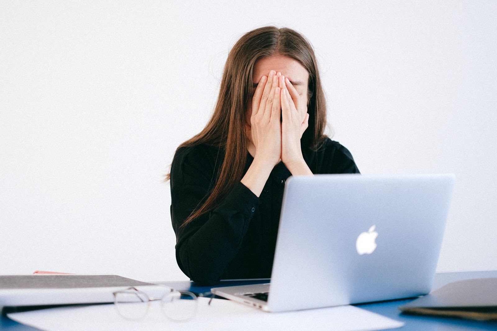 A woman sits with her laptop looking extremely upset and stressed, possibly from an event such as job loss.