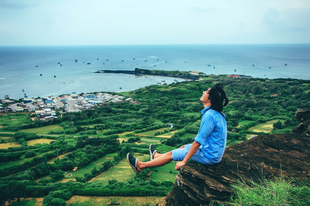Man Smiles Happily Over Grassy Fields While Sitting On Cliff