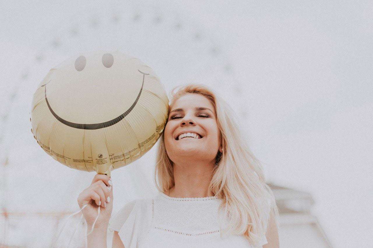 Woman Smiles Joyfully While holding a smiley face balloon next to her face