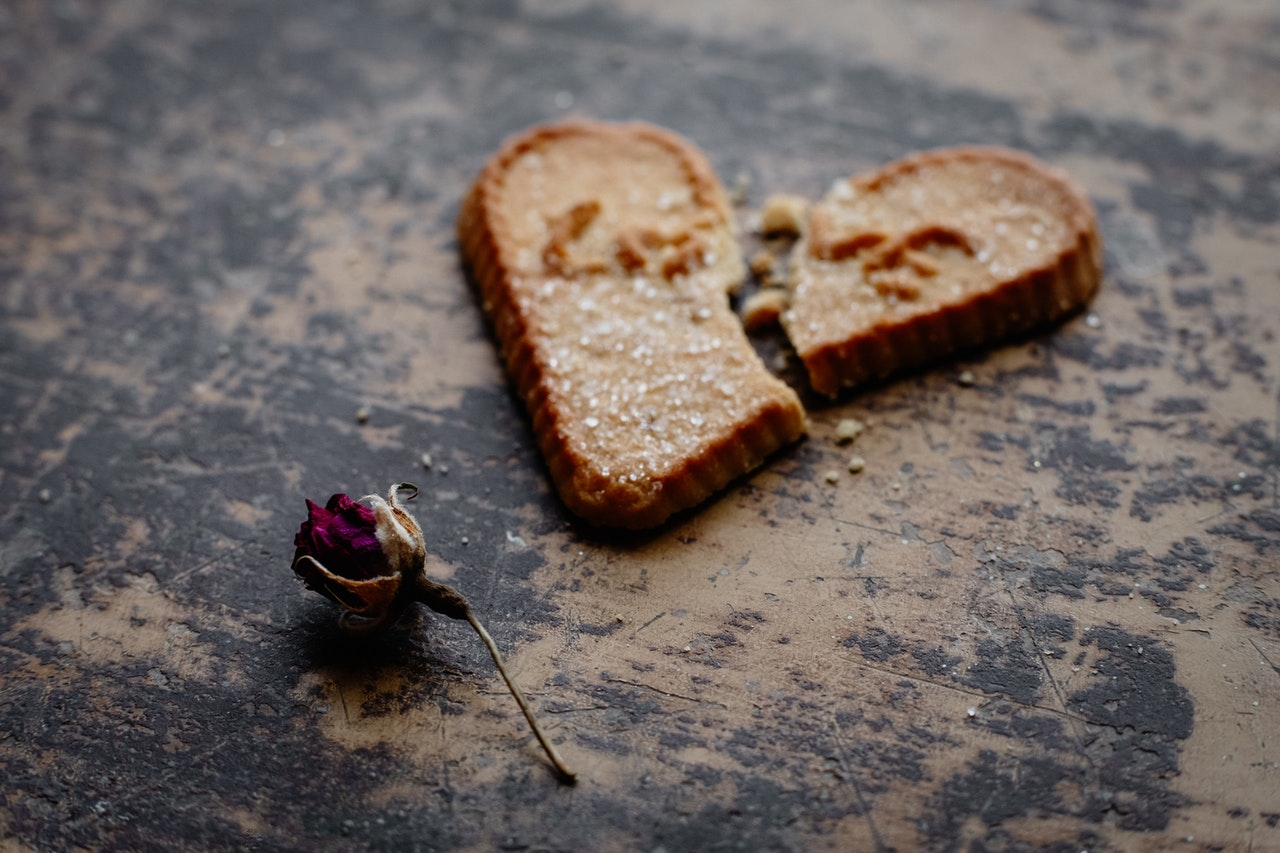 """A cookie with """"love"""" printed on it lies broken in half on a table. A dying rose lies on the below it."""