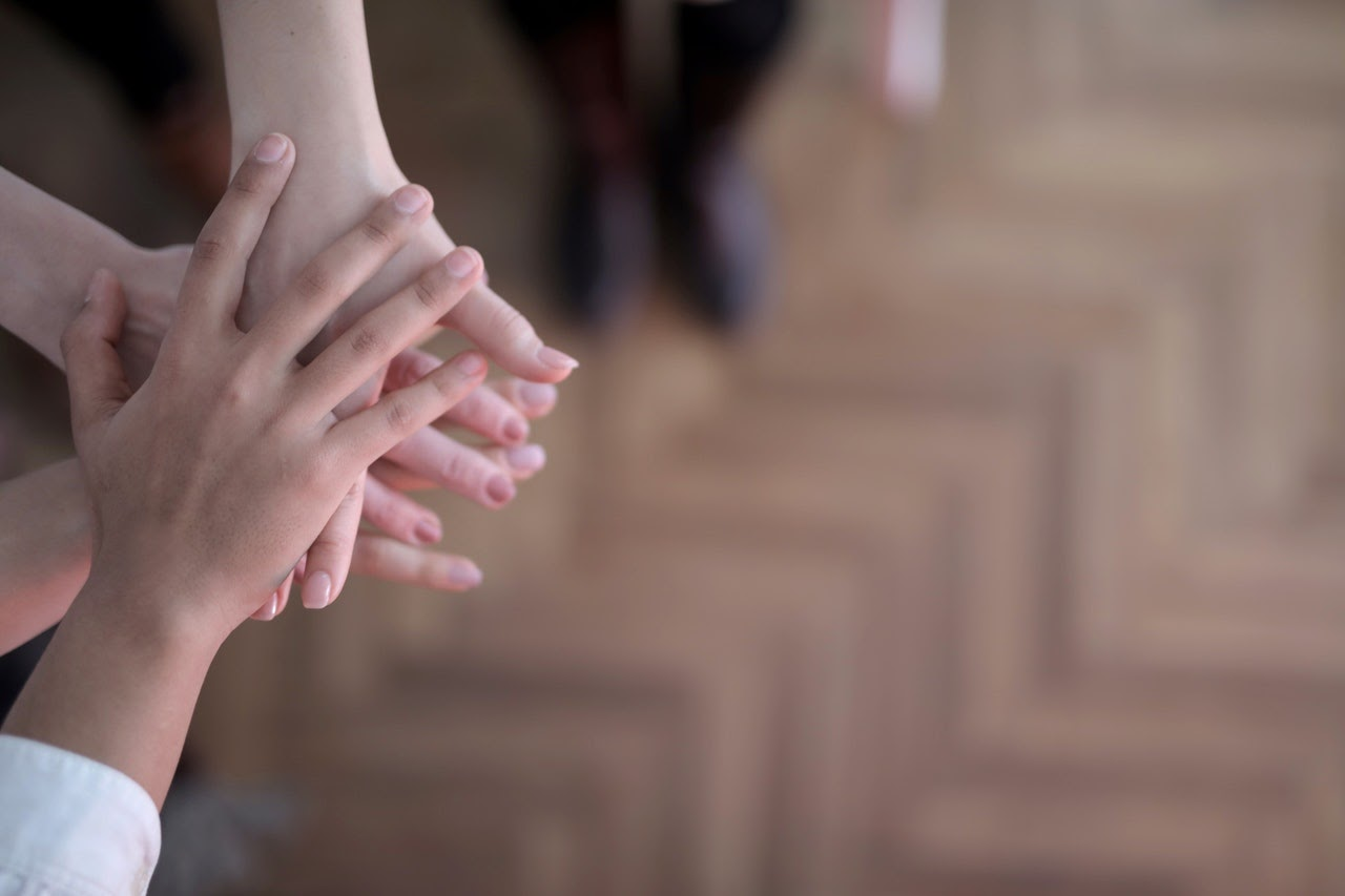 A set of hands rests on top of each other to represent support and unity.