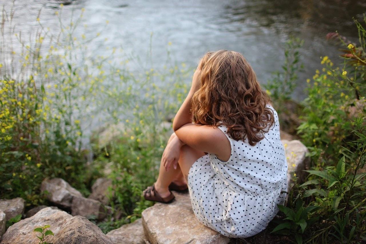 Girl stares sadly at lake