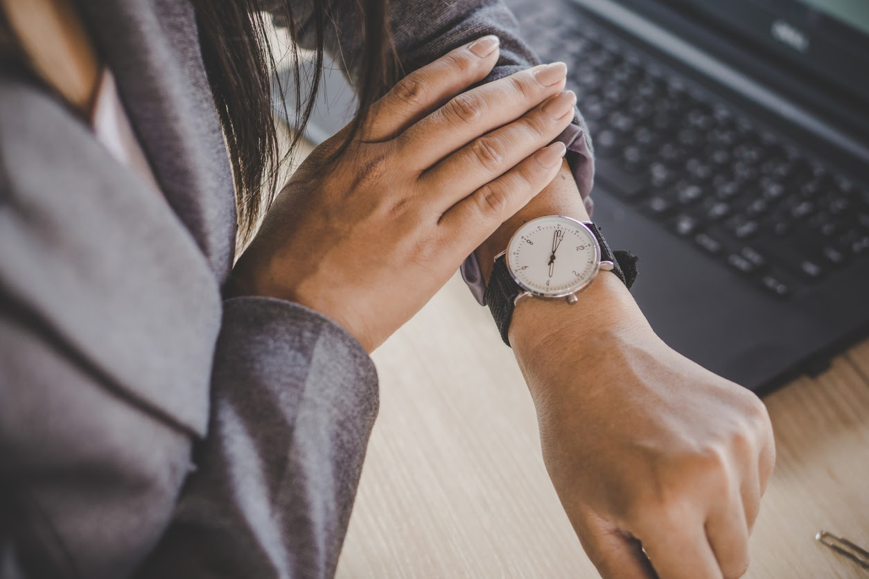 woman checking watch to see if late for TMS treatment
