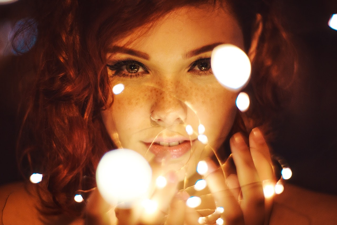 Woman holds string lights in her hands