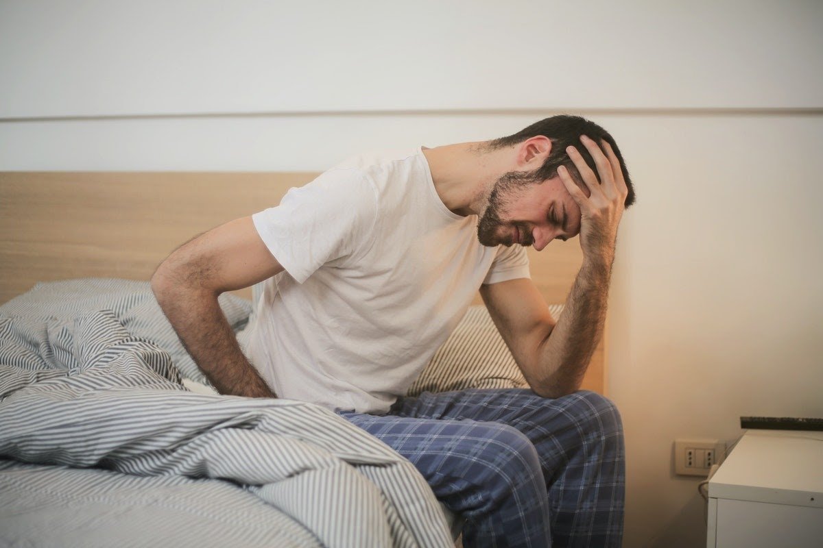 Depressed man in bed considering TMS therapy