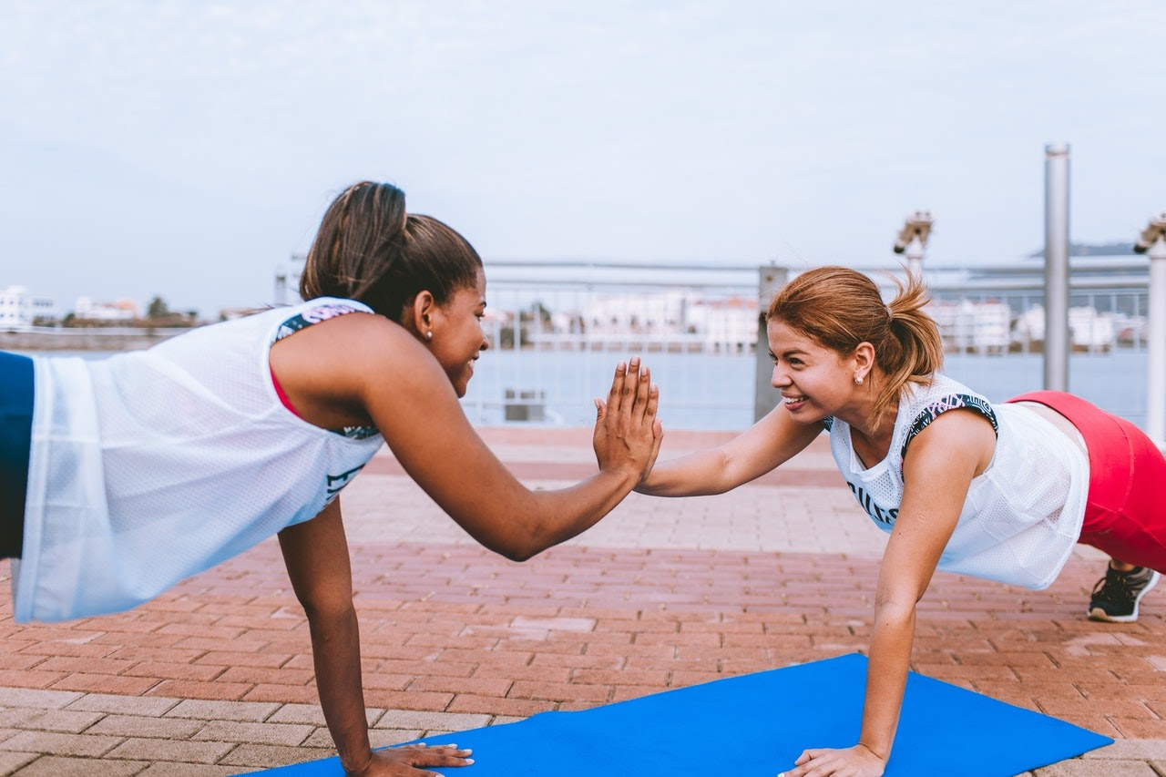 Two young women stretch will doing yoga together and smile