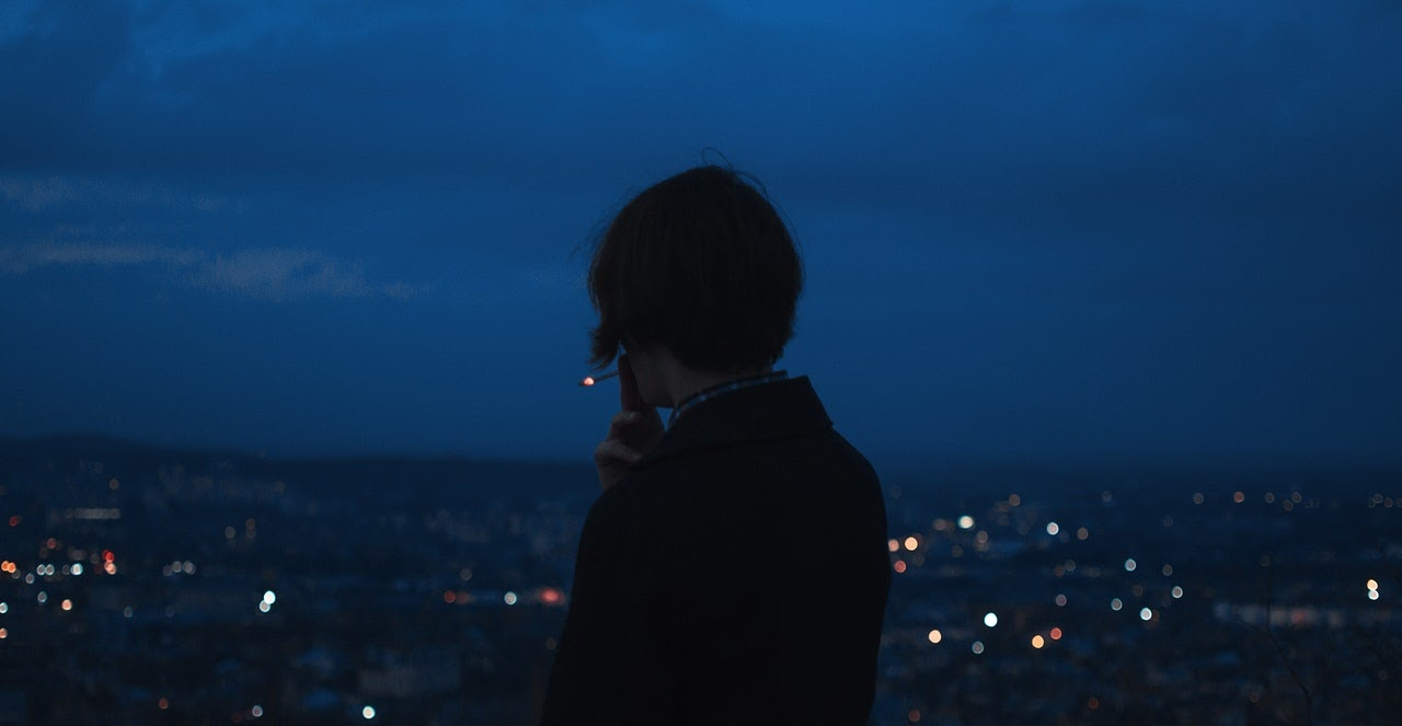 Man smokes a cigarette while looking over a city late in the evening