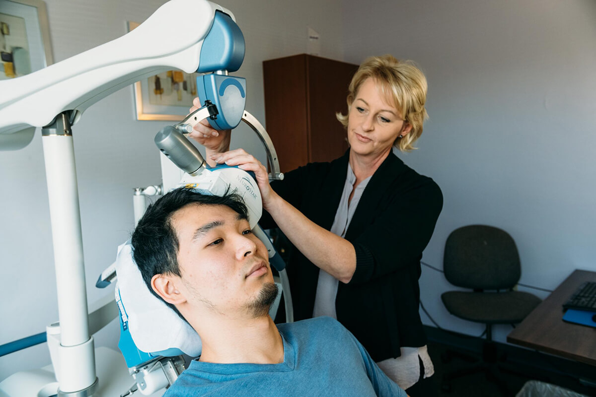 An image of a man receiving TMS therapy with a machine positioned at the front and slightly to the left side of his head.