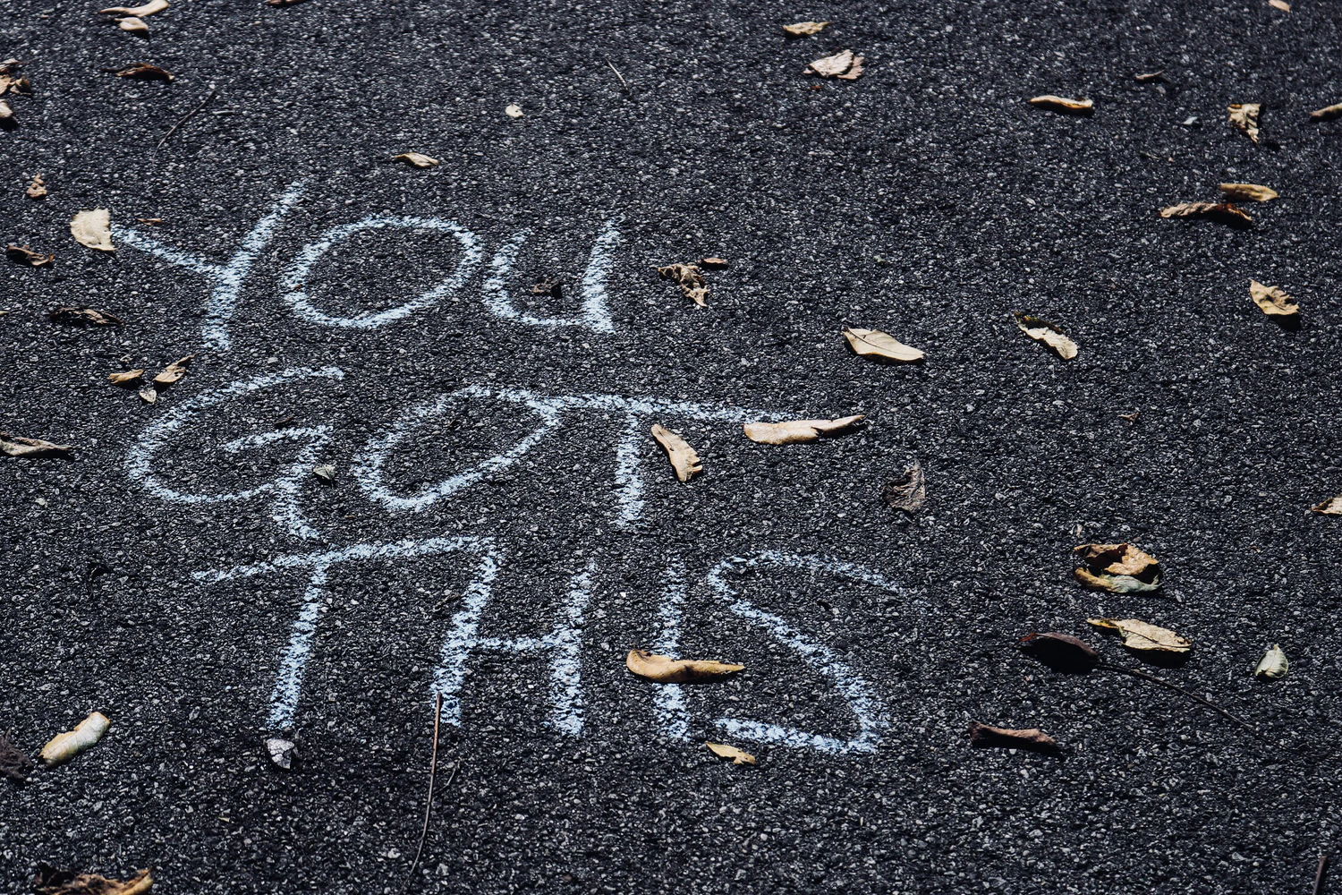 """An image of chalk writing on asphalt, fallen leaves scattered around them. The message reads """"You got this!"""" in all capital letters."""