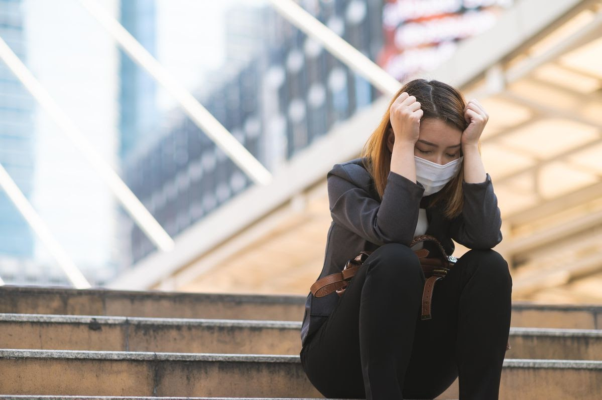 A woman wearing a mask sits outdoors on concrete steps while holding her head in her hands.