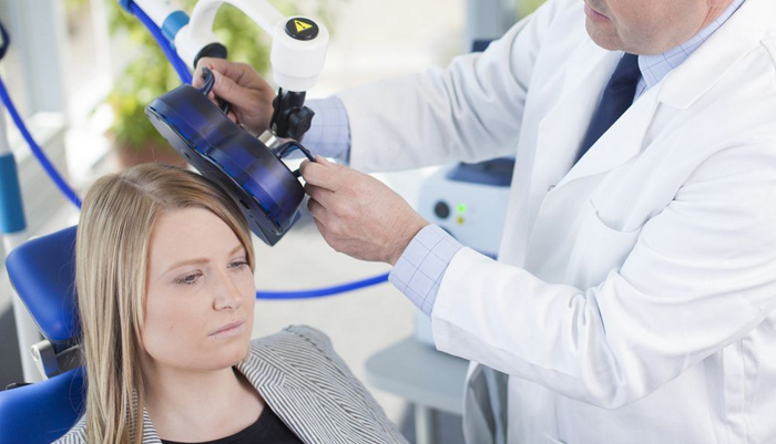 An image of a doctor holding part of a TMS device to a patient's head. Both doctor and patient have very serious expressions.