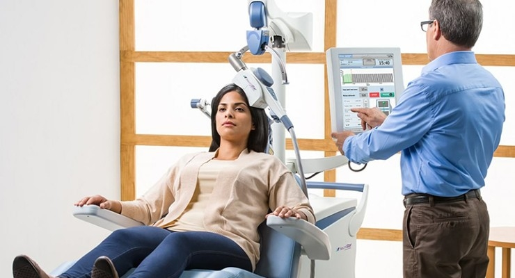 An image of a doctor looking at a monitor connected to a TMS machine that is resting on a patient's head.