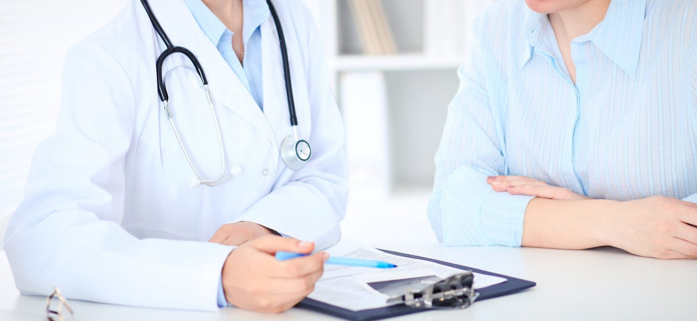 An image of a doctor and a patient sitting at a table from the shoulders down. The doctor is gesturing at something on a clipboard with a pen and the patient is looking at it.