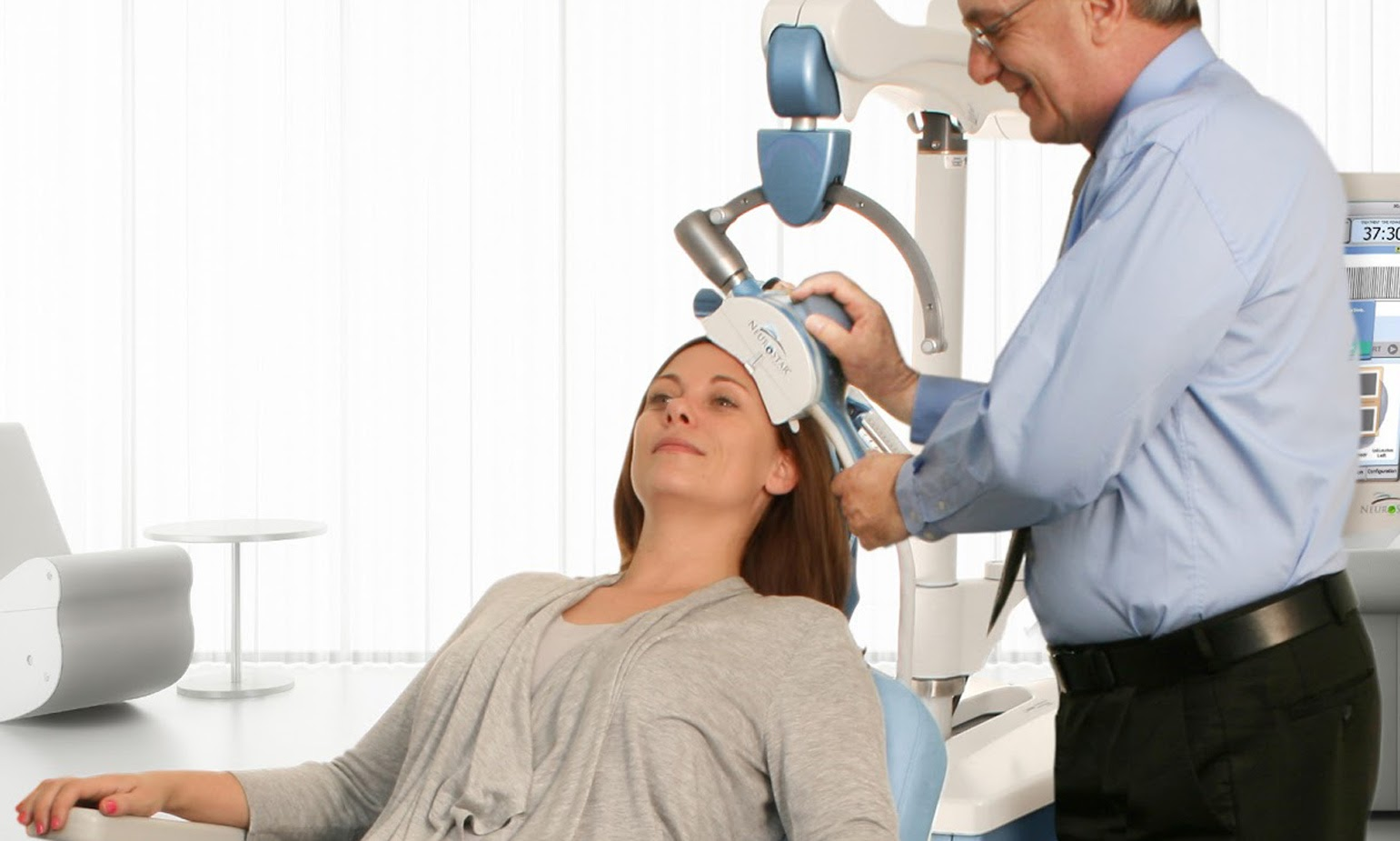 A woman sitting in a doctor's office receives TMS therapy.