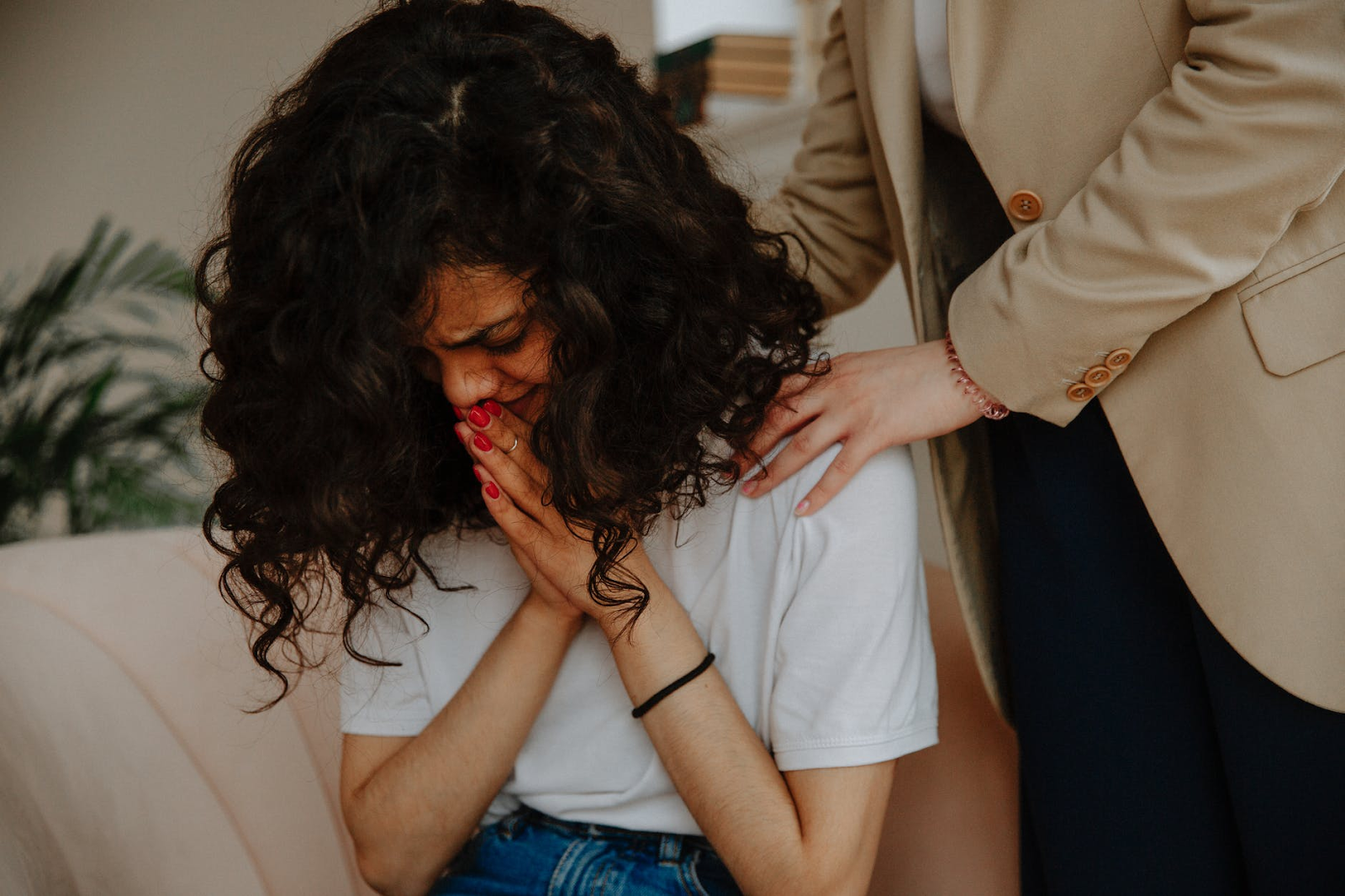 An image of a woman sitting on a couch and crying into her hands, which are pressed together. Someone stands behind her, their face out of frame, with both of their hands on her shoulders in comfort.
