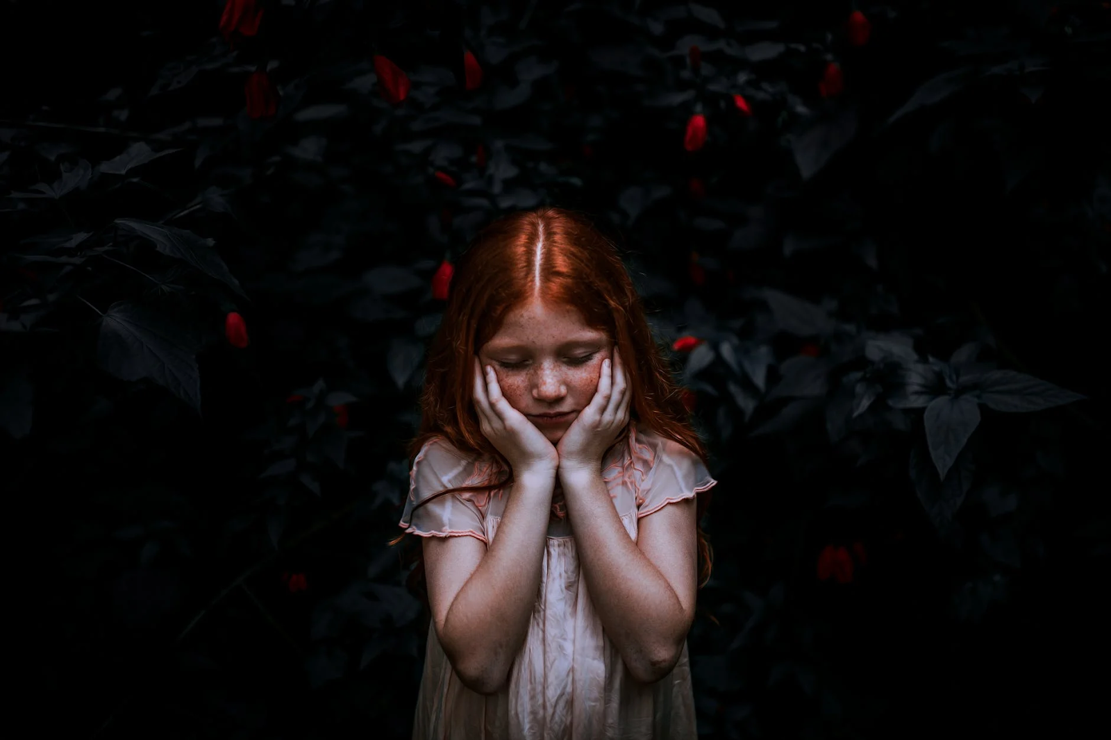 An image of a little red-haired girl standing by herself in the dark in front of a tree with red flowers. She has her face in her hands and her eyes closed.