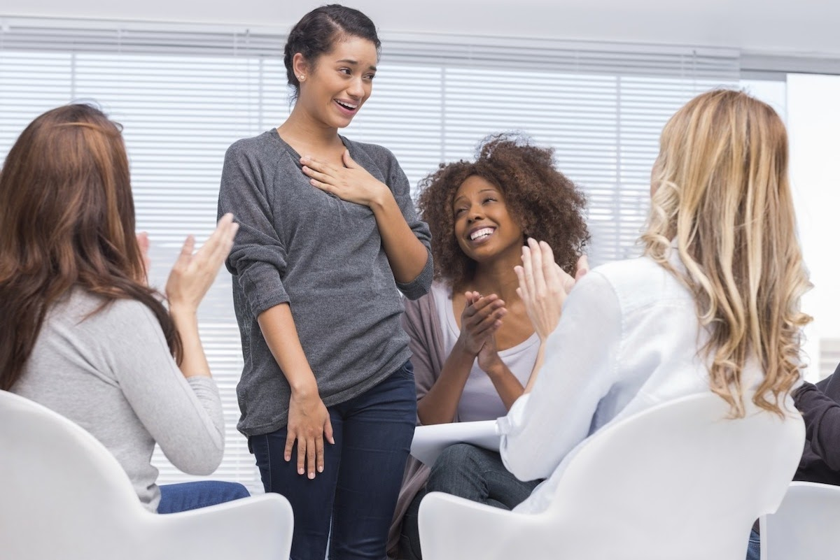 Women in a support group applaud a woman standing up.