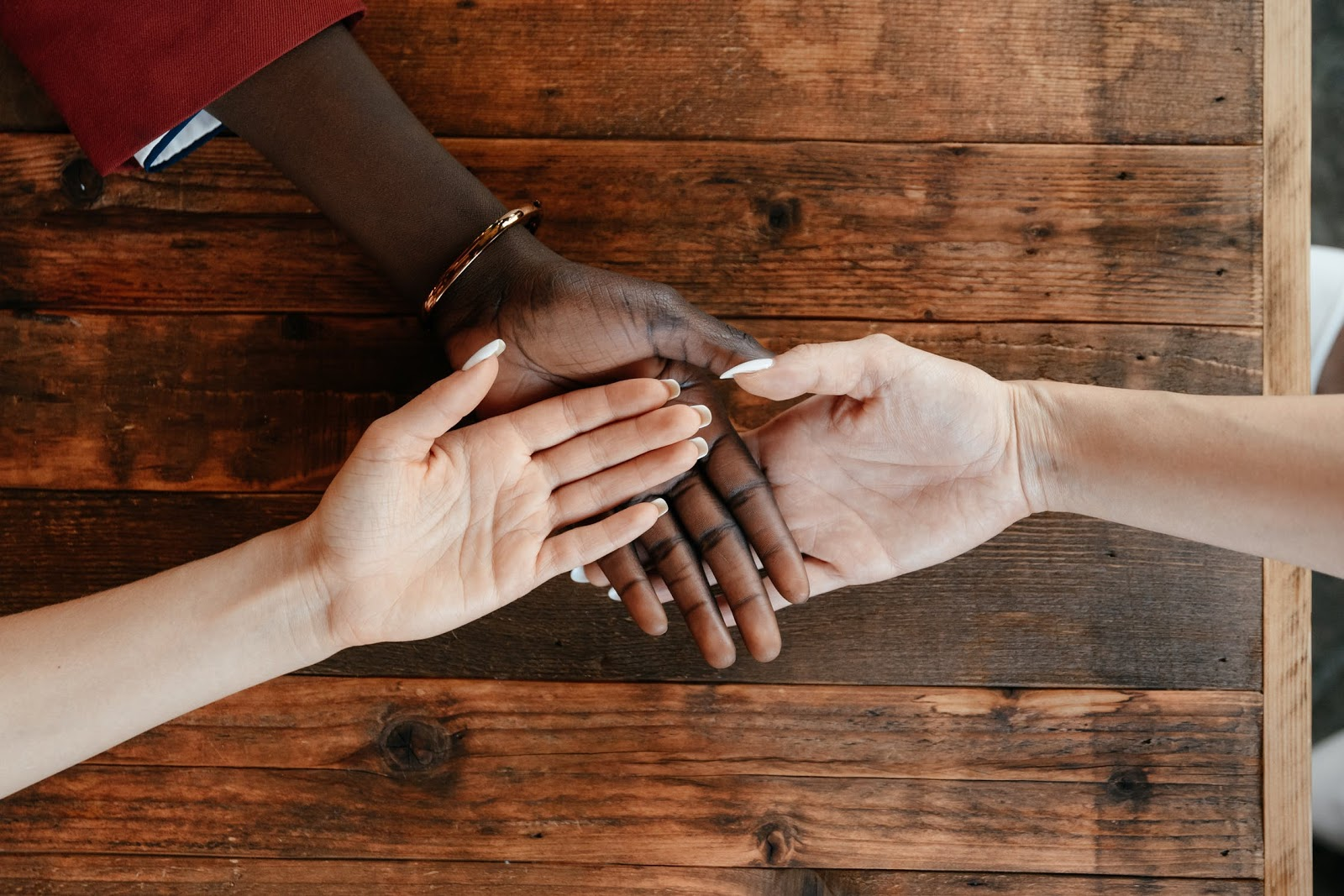 Three people touch hands in the middle of a table