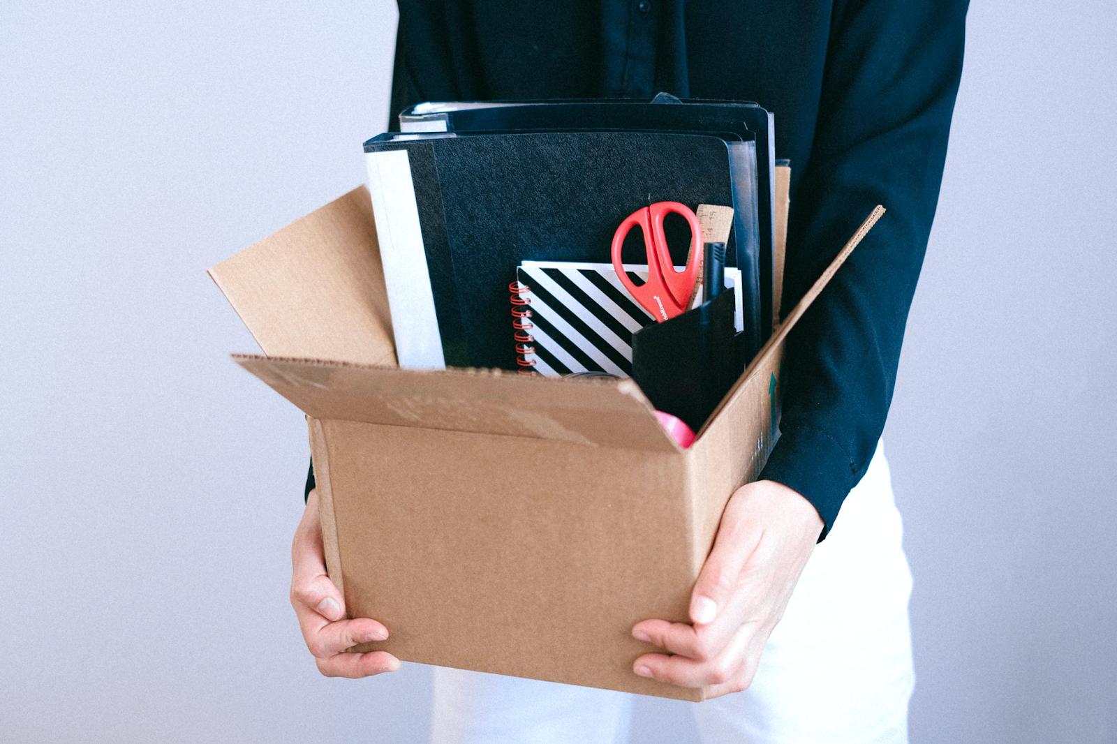 An image of a woman carrying a cardboard box full of office supplies, including a notebook, binders, and a pencil cup.
