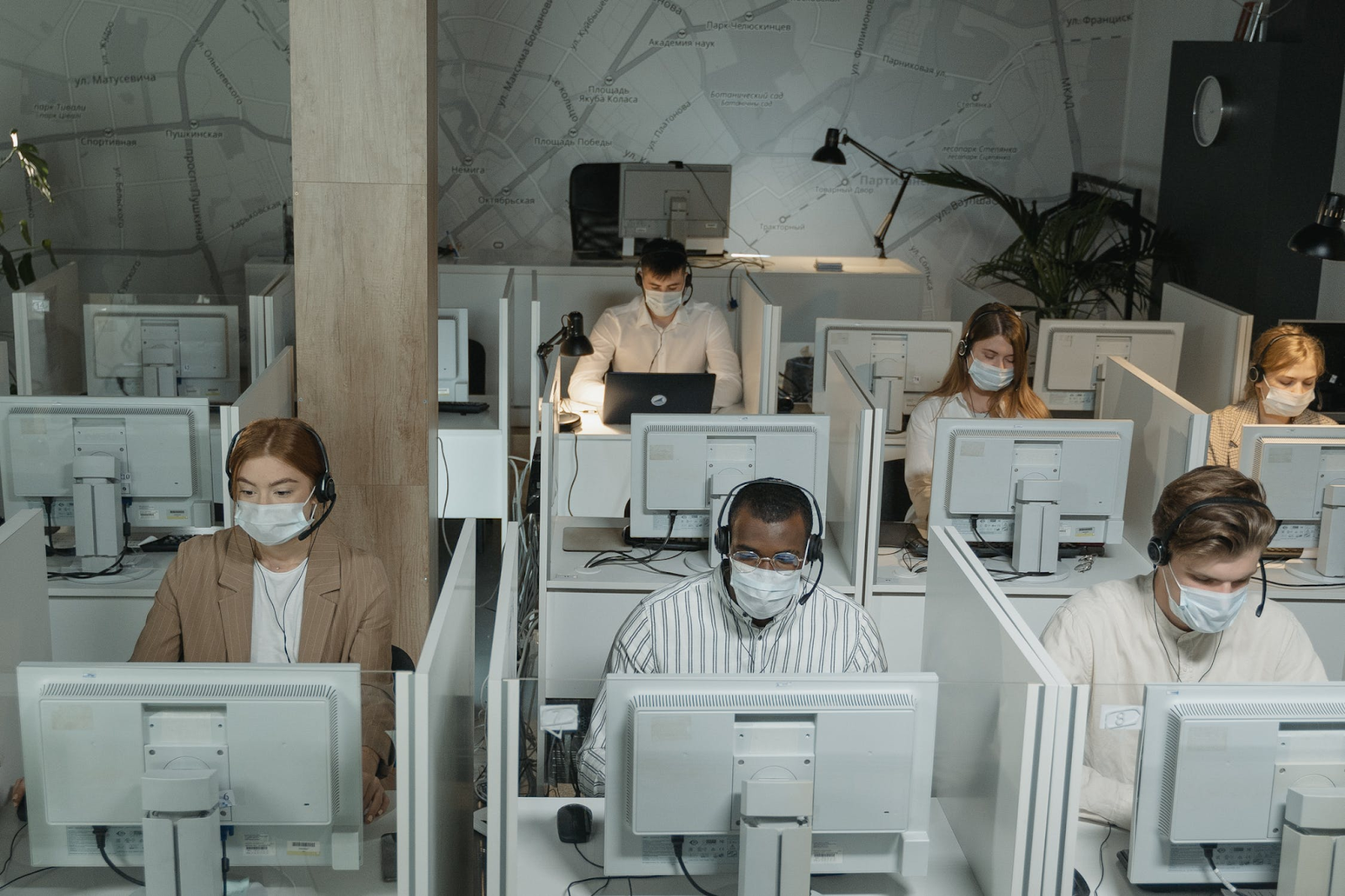 An image of a muted-colored office space full of identical computers in identical cubicles. All of the people sitting at their desks are wearing masks.