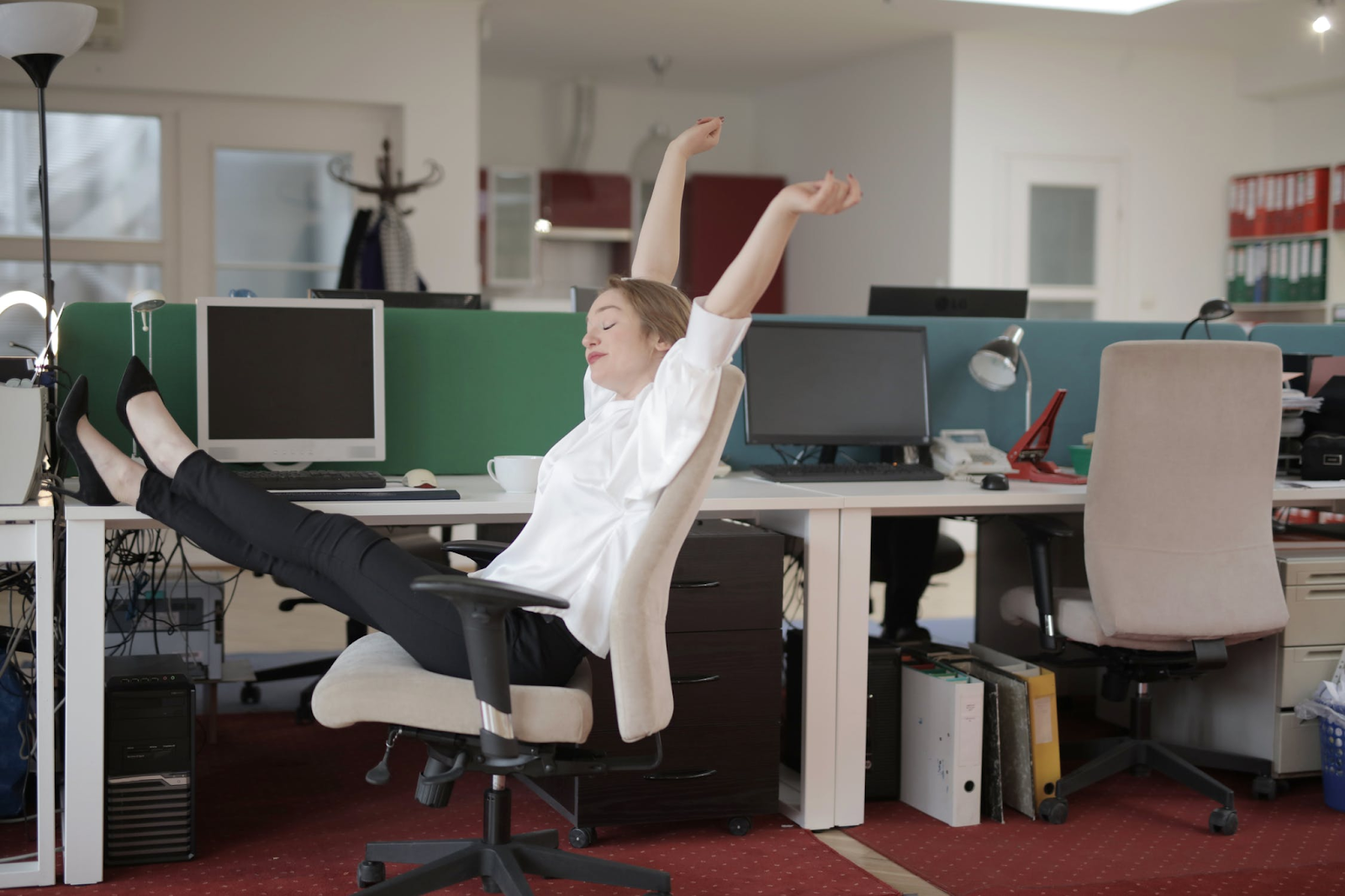 An image of a woman leaning back and stretching in her office chair, her arms in the air and her legs propped up on the desk.