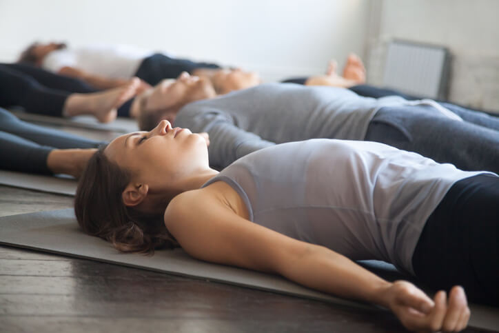 An image of several people laying on yoga mats on a wooden floor, their arms resting at their sides and their eyes closed in meditation.