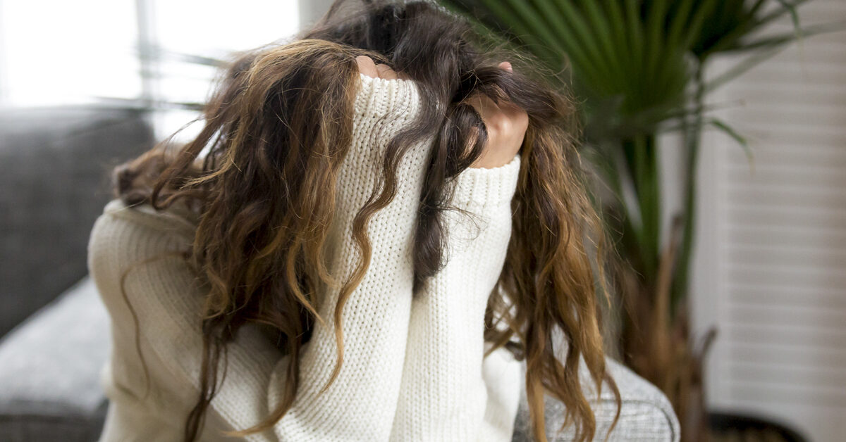 An image of a woman having a panic attack. She is sitting curled up on the floor with her hair bunched up in her fists, obscuring her face.
