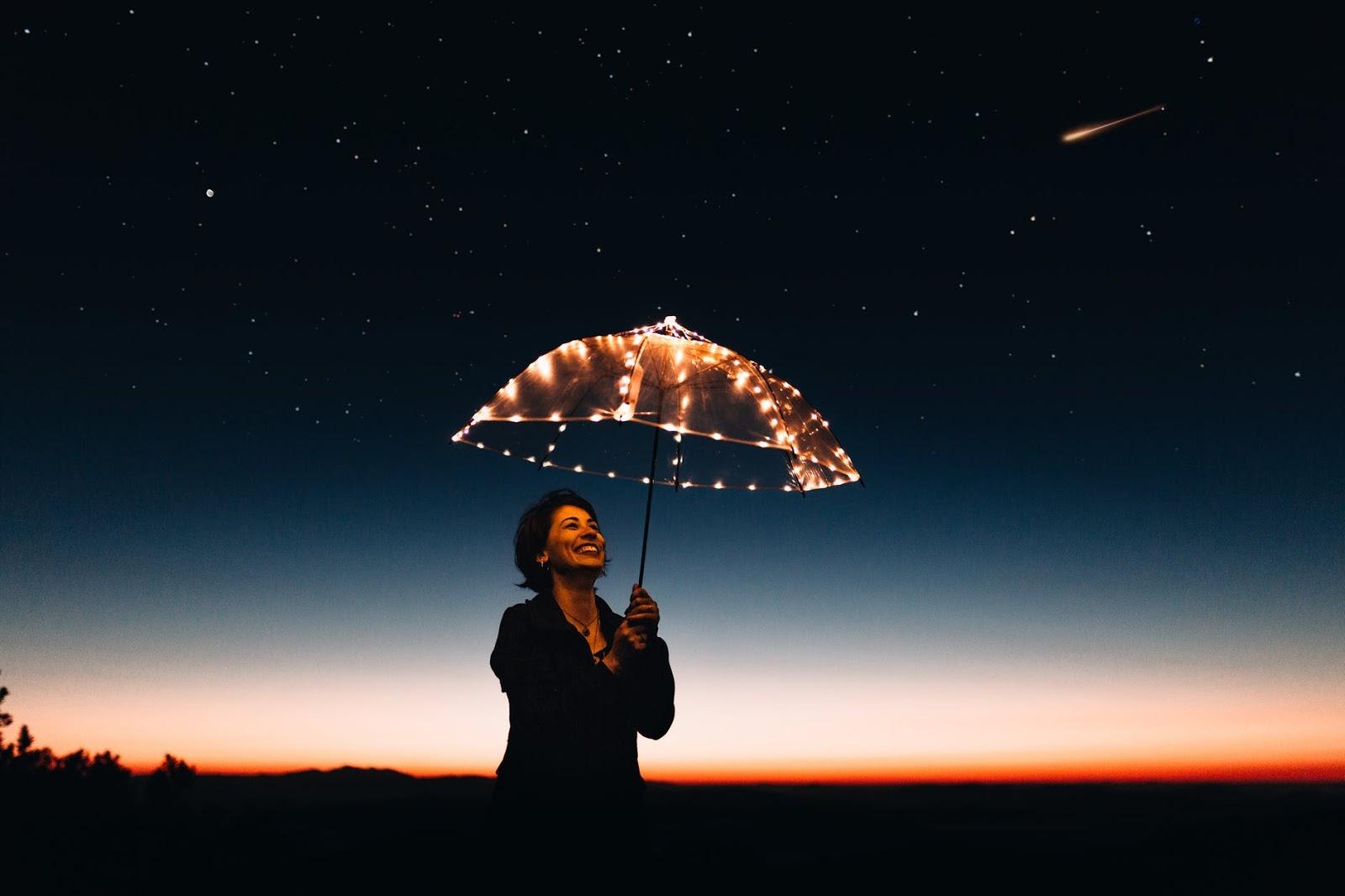A woman, smiling, holding an illuminated umbrella at dusk