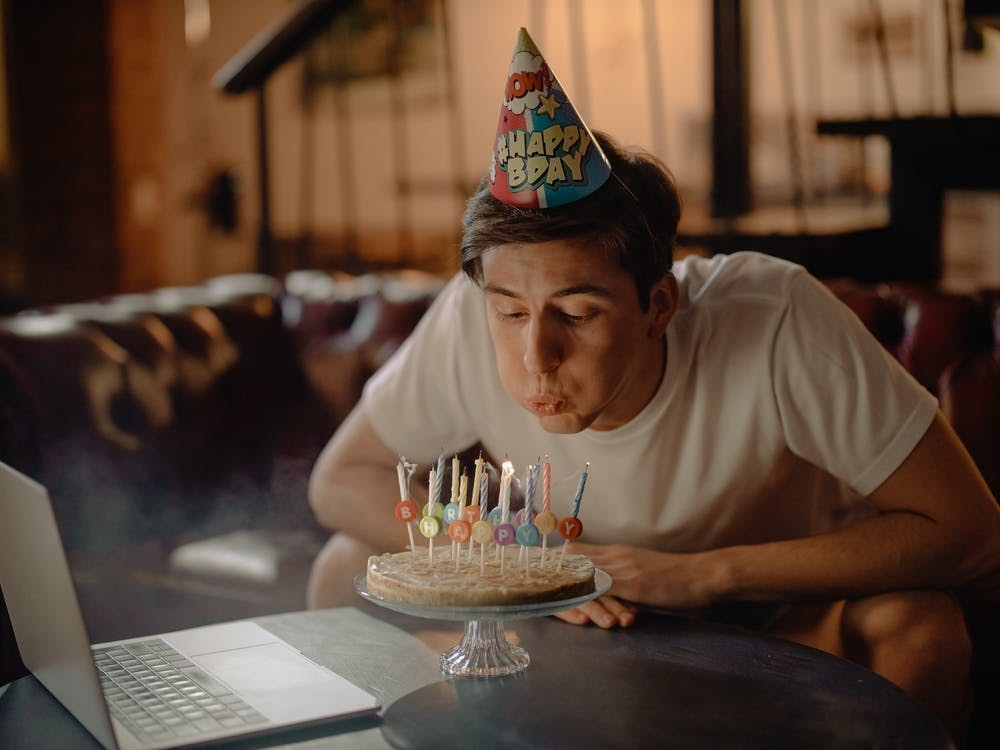 A young adult man in a birthday hat blows out his birthday cake candles alone in front of a laptop