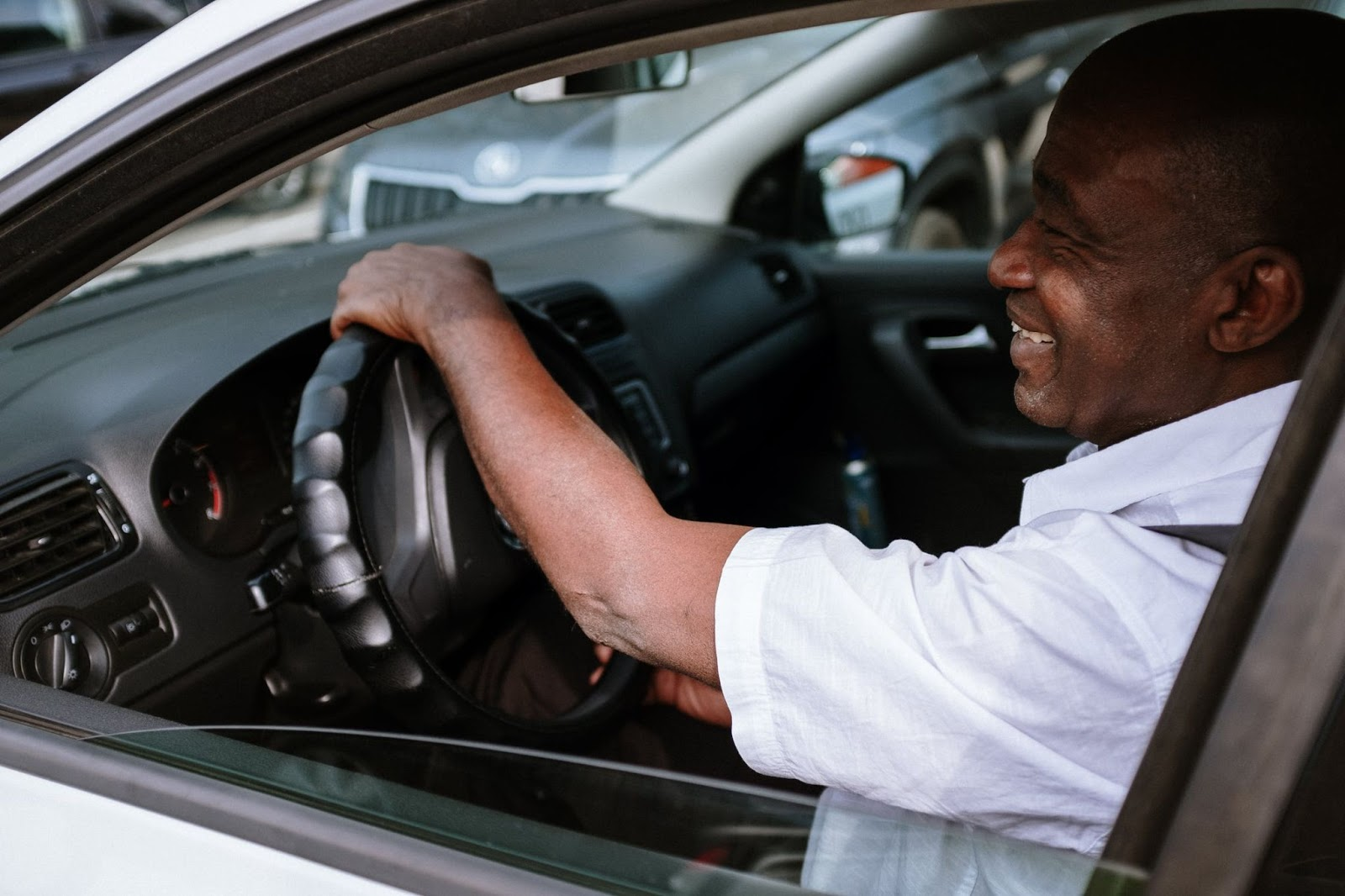 An older man in a white shirt smiles as he drives his car with the window rolled down