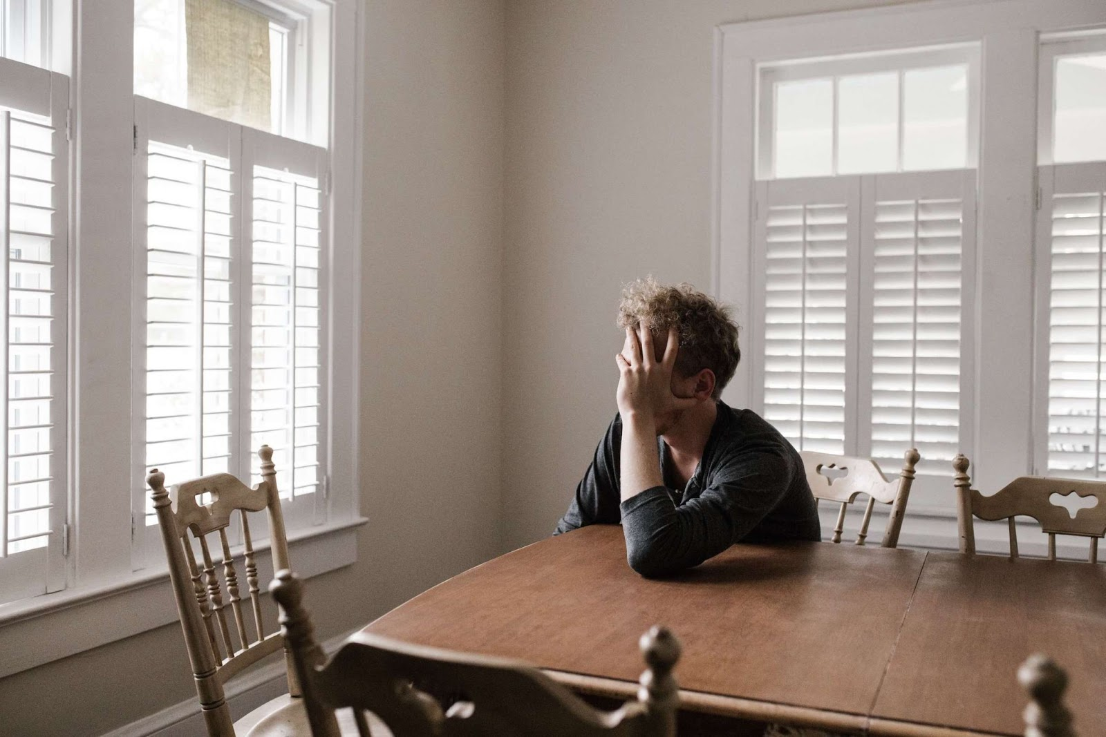 A man at his kitchen table holds his head in his hand, face obscured, as he stares out the window