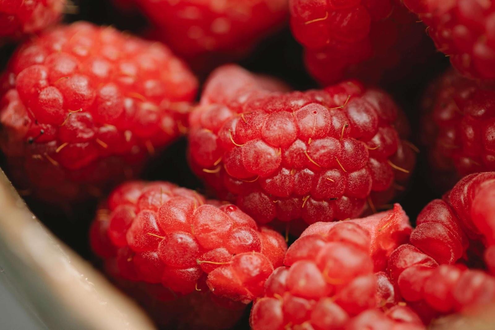 Red, juicy raspberries in a bowl.