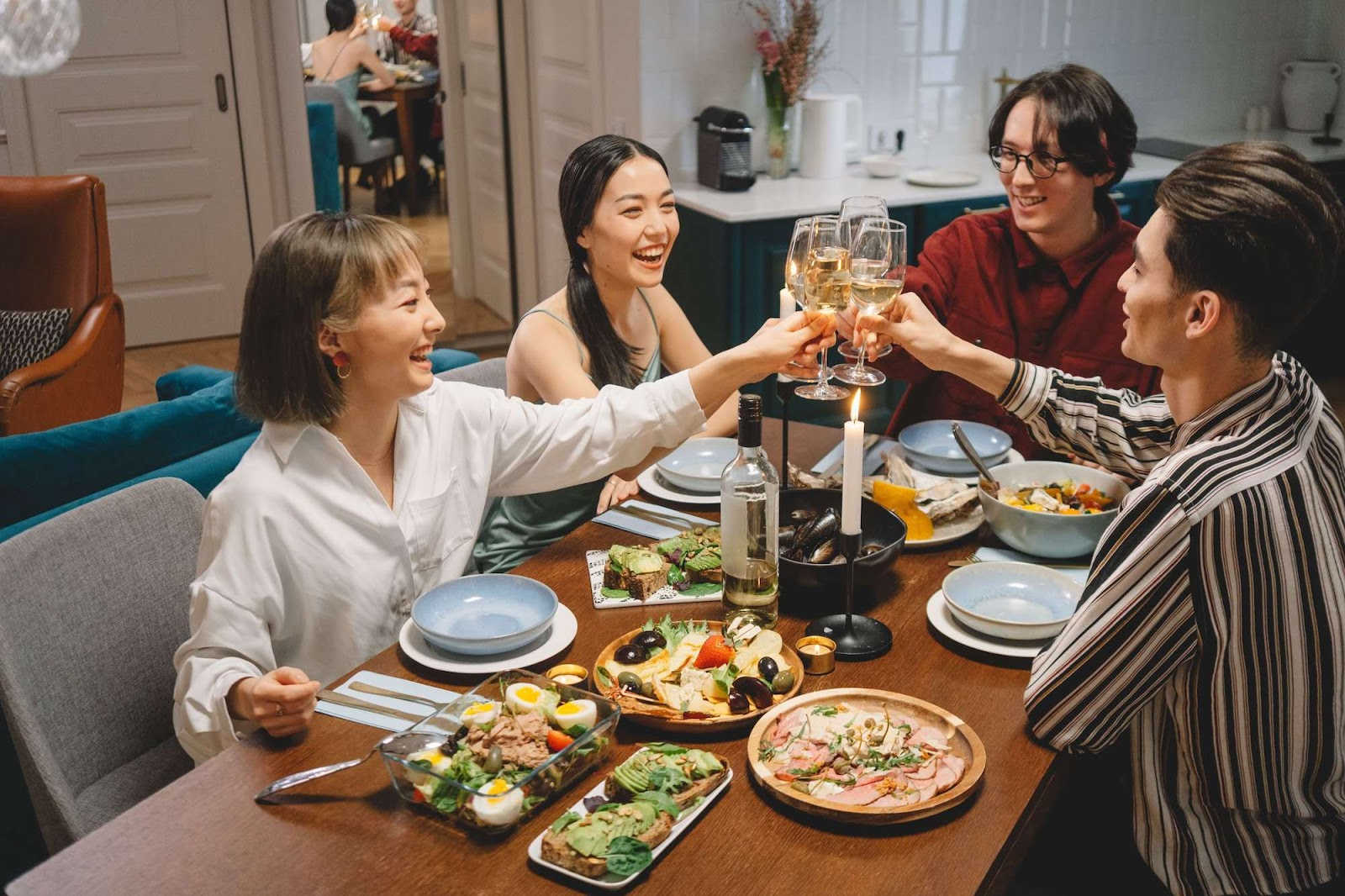 A group of people, two men and two women, toasting and smiling over a healthy meal
