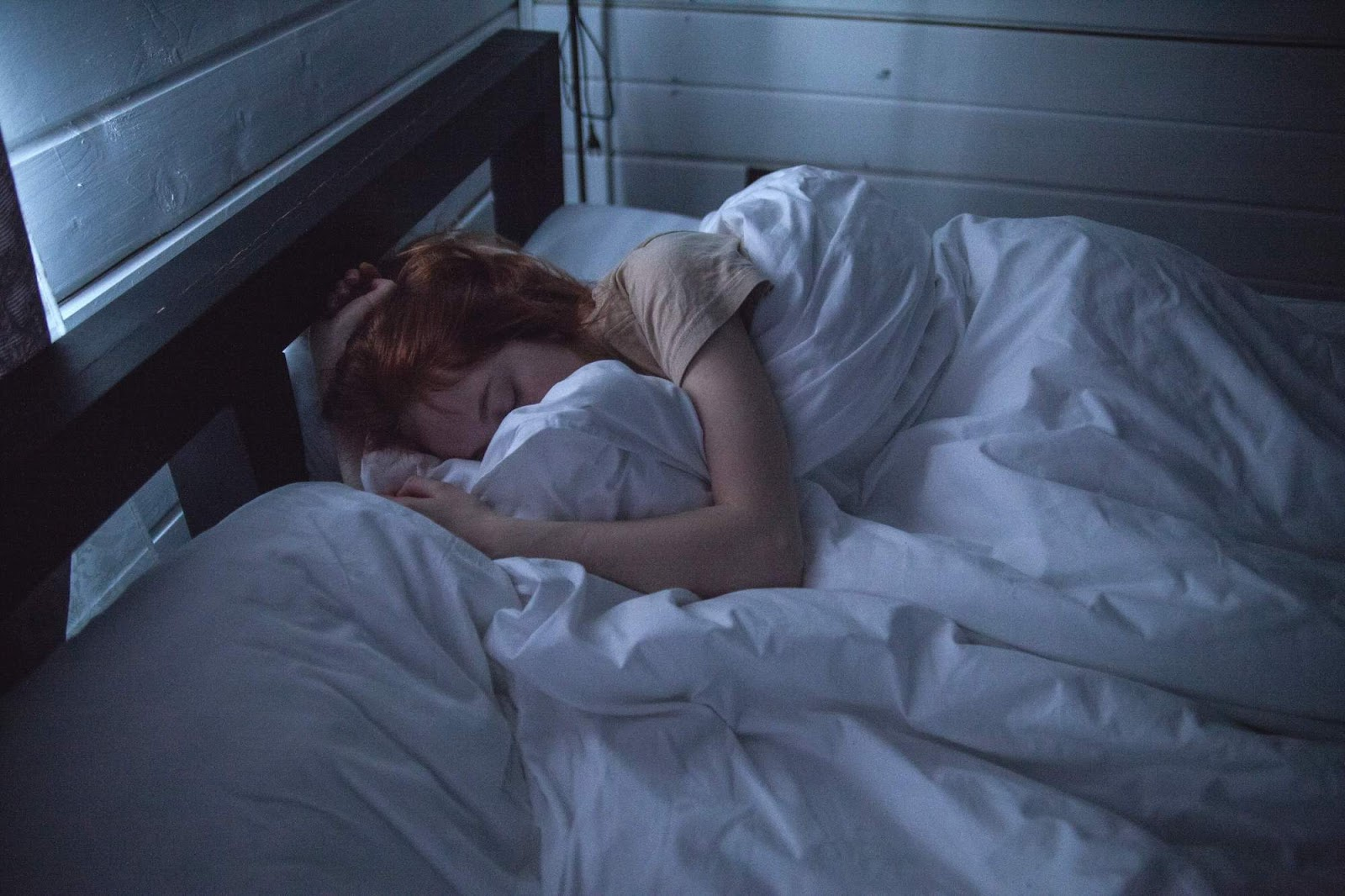 A red-haired woman asleep in a bed with white sheets