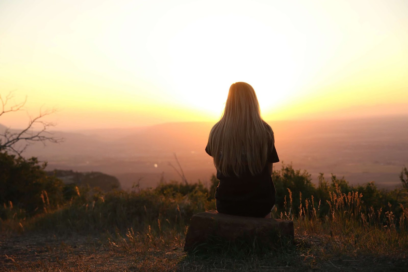 A woman, her back turned, watching a hazy golden sunrise from atop a hill