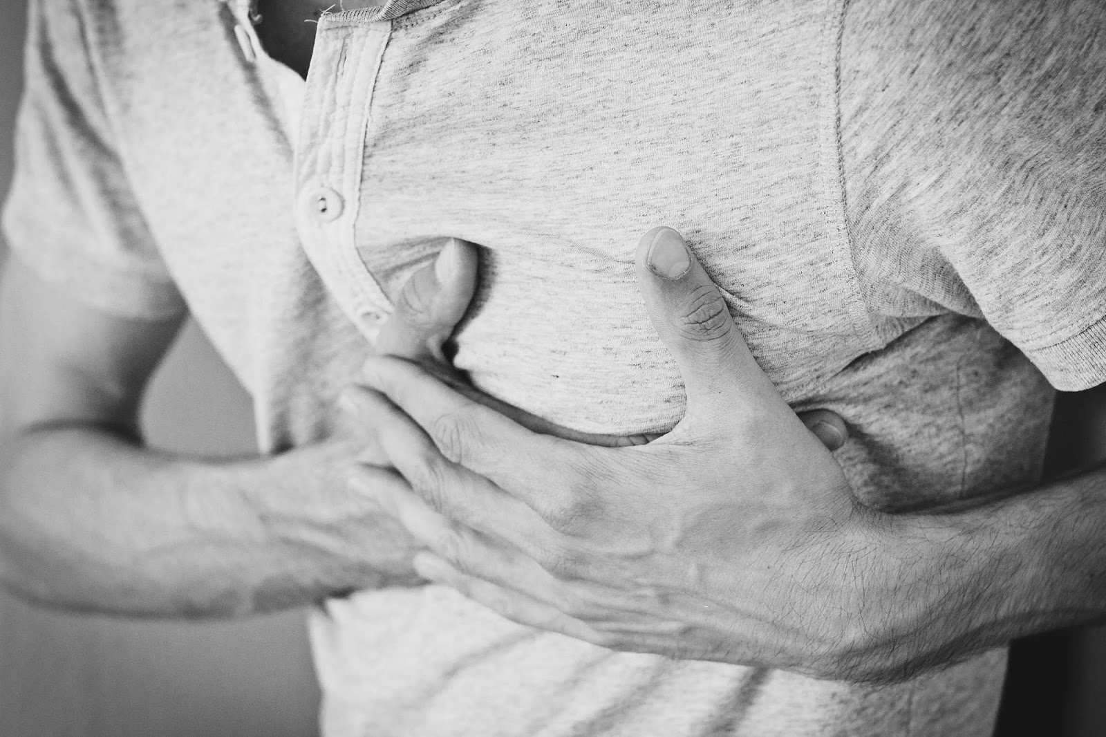 A man holding his chest, over his heart, in two hands. Black and white filter.