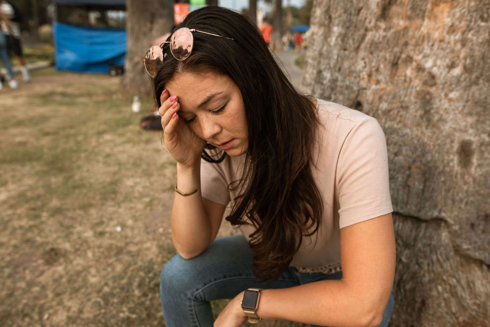 A confused woman holding her head as she sits against a tree